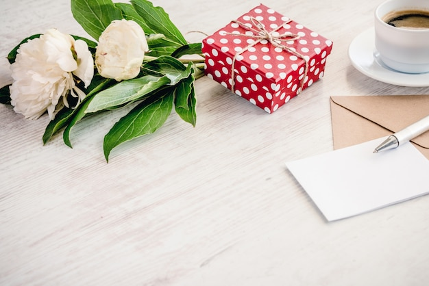 Red dotted gift box, kraft envelope and empty greeting card, coffee cup and peony flowers bouquet over white wood , copyspace.