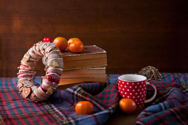 화환이 있는 스코틀랜드 담요에 핫 초콜릿을 넣은 빨간 점선 머그 또는 차 컵. 책과 함께 아늑한 집 개념입니다. 축제의 핫초코 한 잔. 전통적인 수제 크리스마스 코코아와 만다린 오렌지