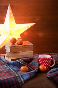 Red dotted mug or tea cup with hot chocolate on a scottish blanket. cozy home concept with books. a cup of festive hot chocolate. traditional homemade christmas cocoa and mandarin orange citrus