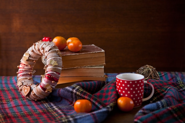 Red dotted mug or tea cup with hot chocolate on a scottish blanket with wreath. cozy home concept with books. a cup of festive hot chocolate. traditional homemade christmas cocoa and mandarin oranges