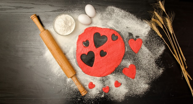 Red dough, cut out hearts, flour, eggs and rolling pin on a black background, space for text