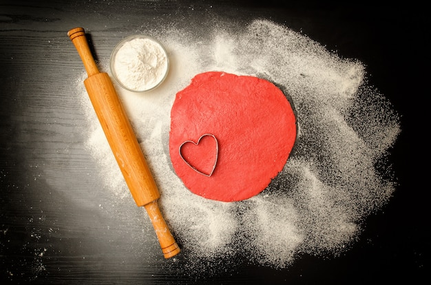 Red dough to form cut-out hearts and flour on the black table, a rolling pin. top view