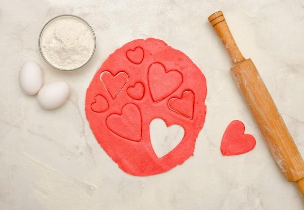 Красное тесто скалкой и вырезать сердечки на белом столе, яйца, крупный план
