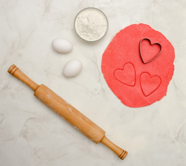 Red dough with a cut out heart, eggs, flour and rolling pin,on a white table. top view, space for text
