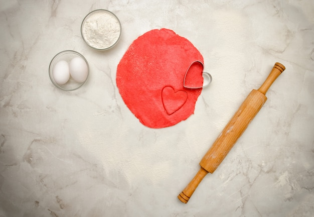 Red dough with a cut out heart, rolling pin, eggs and flour on a white table. top view, space for text