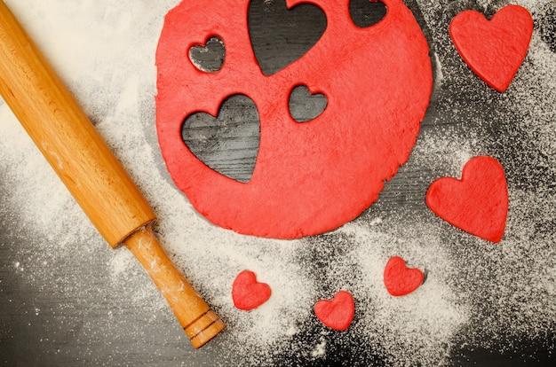 Красное тесто с вырезанными сердечками и мукой на черном столе, скалкой