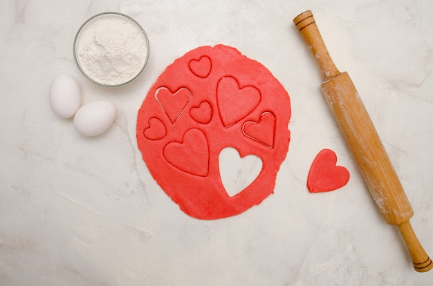 Red dough with a cut out hearts, eggs, flour and rolling pin,on a white table. top view