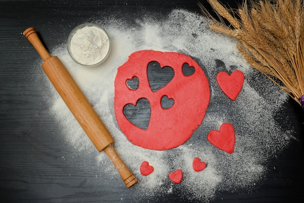 Red dough with cutout hearts and flour on the black table top view