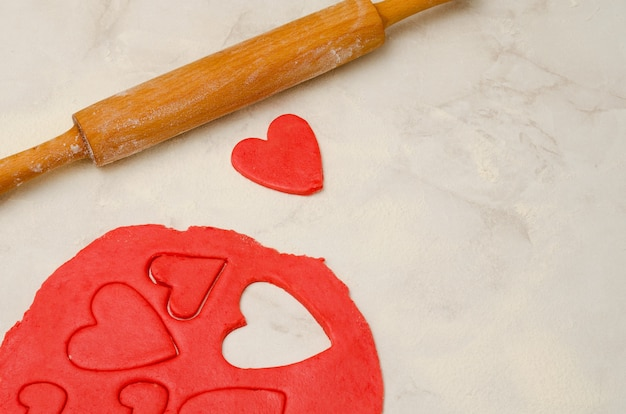 Red dough with a rolling pin and cut out hearts on a white table, close-up. space for text