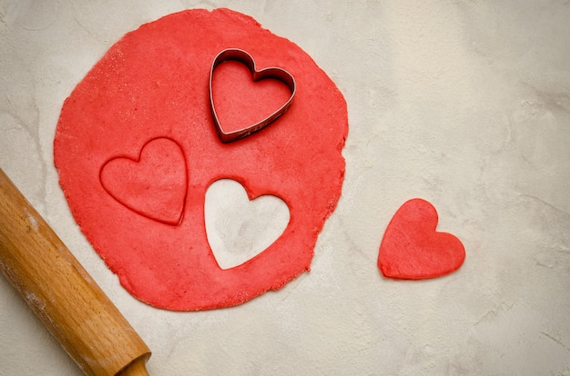 Red dough with a rolling pin and cut out hearts on a white table, close-up