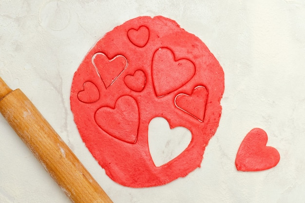 Red dough with a rolling pin and cut out hearts on a white table. top view