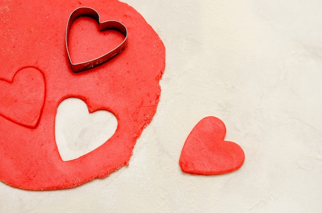 Red dough with a shape to cut and cut out hearts on a white table, space for text, close-up