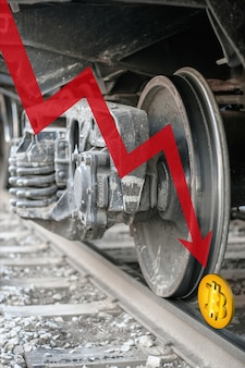 Red down arrow and bitcoin on rails under a train wheel. bitcoin is crushed and fell down. cryptocurrency trading crisis. crash btc. vertical.