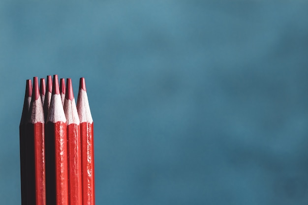 Red drawing pencils isolated over the gray background