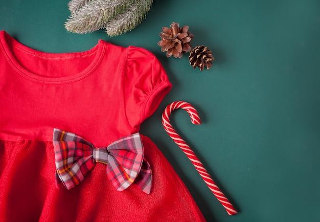 市松模様の弓、タイツ、緑の背景にキャンディー杖と赤いドレス