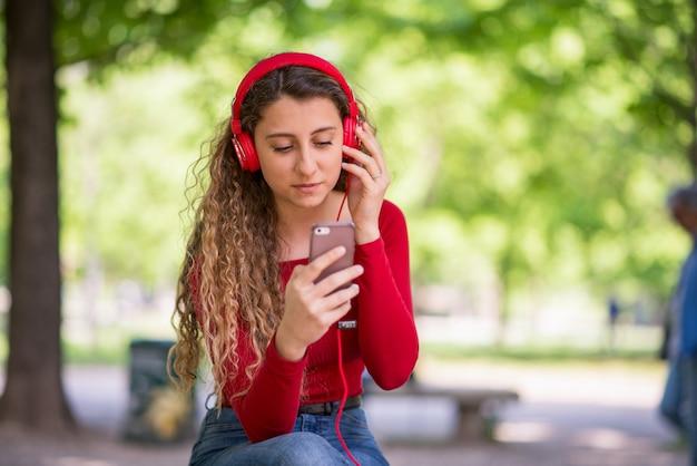 Красный одетый подросток, слушающий музыку с телефона в парке