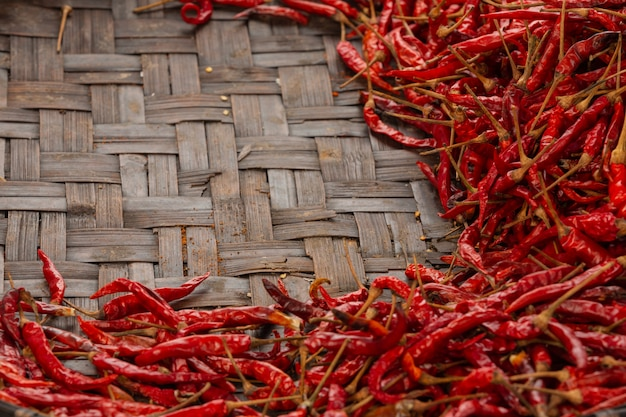 Red dried chilies placed on the space on the weave.