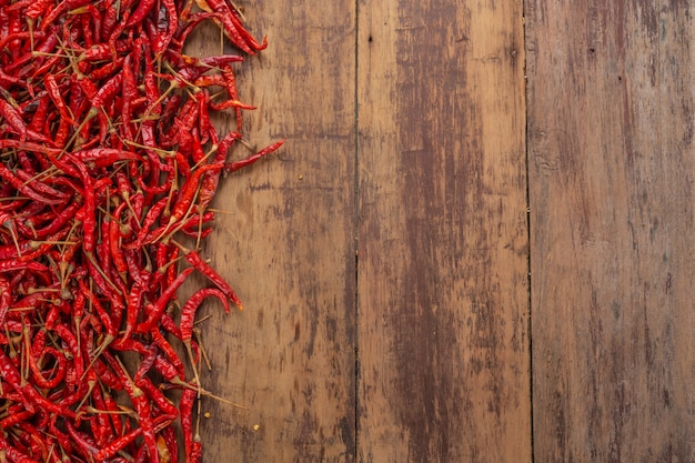 Red dried chilies that are stacked on the plank.