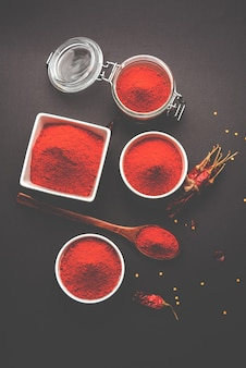 Красное сушеное мирчи мирчи или холодный порошок в миске на мрачном фоне, выборочный фокус