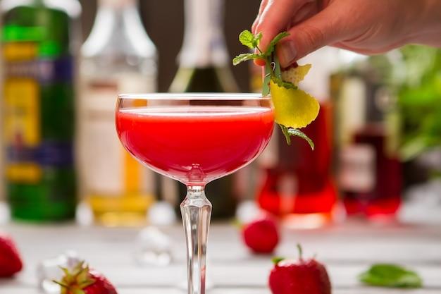 クーペグラスの赤い飲み物。ミントの小枝を持つ男性の手。クローバークラブの特別レシピ。バーテンダーの仕事。
