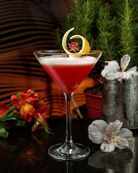 Red drink in martini glass with lemon zest garnish in dim-lit bar with flowers