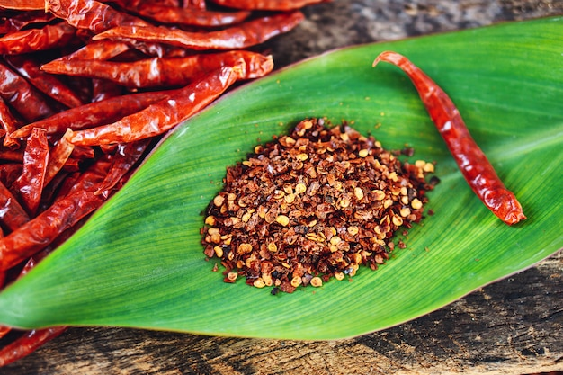 Red dry chili peppers and chili powder on green leaf closeup