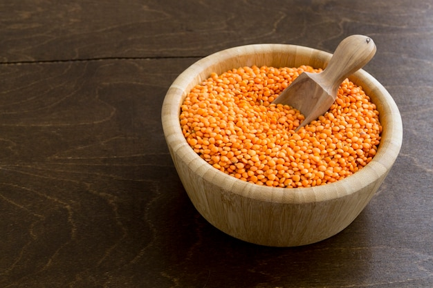 Red dry lentils in a bamboo bowl.