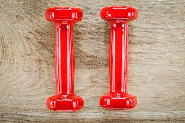 木の板のフィットネスの概念に赤いダンベルの重み