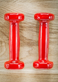 木の板に赤いダンベルウェイトスポーツトレーニングのコンセプト