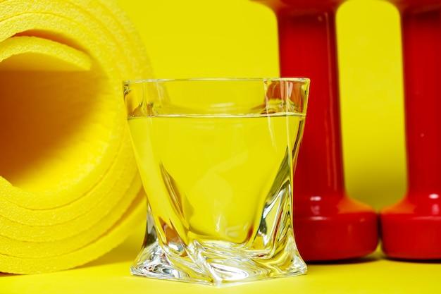 Красные гантели, стакан воды, желтый коврик, цветной фон, спорт, энергетический напиток, оборудование для тренажерного зала