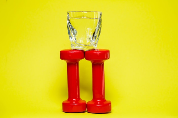 Red dumbbells, a glass of water, colored background, sports, energy drink, equipment for the gym