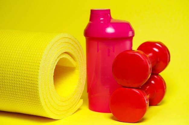 Красные гантели, розовый шейкер, желтый коврик, цветной фон, спорт, энергетический напиток, тренажеры