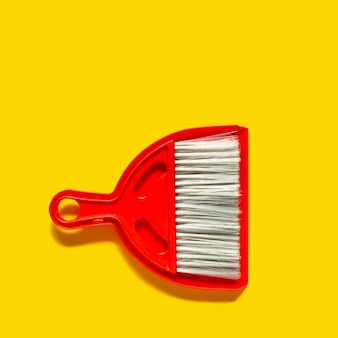 Red dustpan and brush lying on yellow background