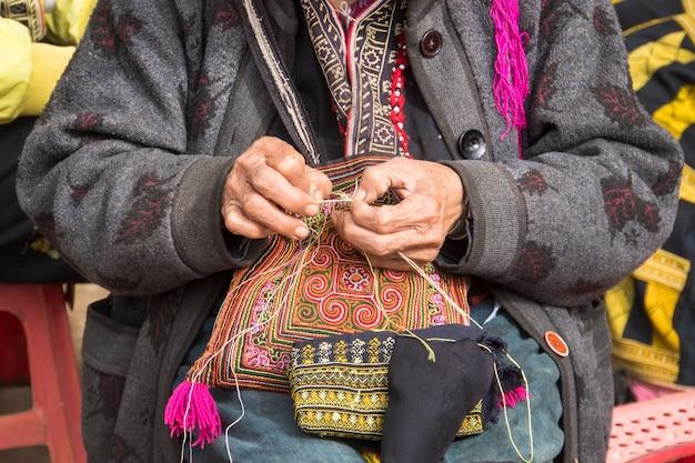 ベトナム、ラオカイ県サパで縫製している赤いdzao少数民族の女性。年配の女性が路上でお土産を作っています。 ta phin、lao cai、ベトナム-2019年1月12日