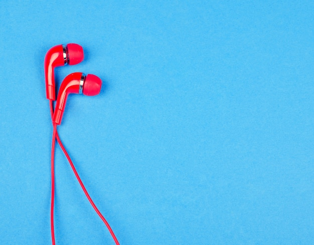 Red earbud headphones on a blue background