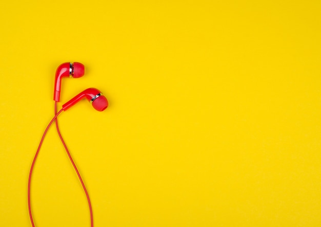 Red earbud headphones on a bright yellow background