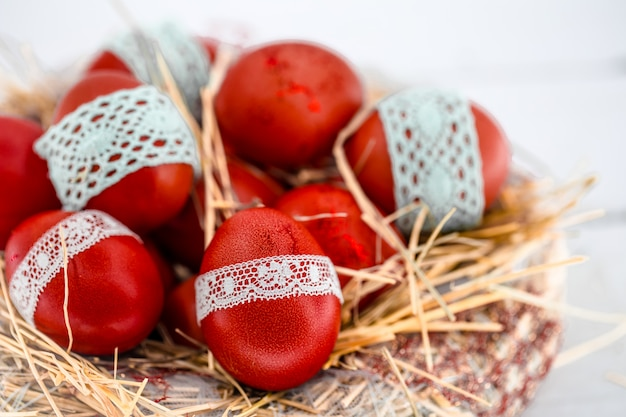 Red easter eggs in a nest of hay, tied a lace ribbon, close-up, lying on a white wood