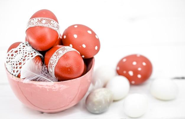 Красные пасхальные яйца на белой кружевной ленте, крупным планом