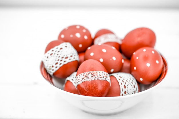 Red easter eggs on a white plate and on white tied lace tape, close-up