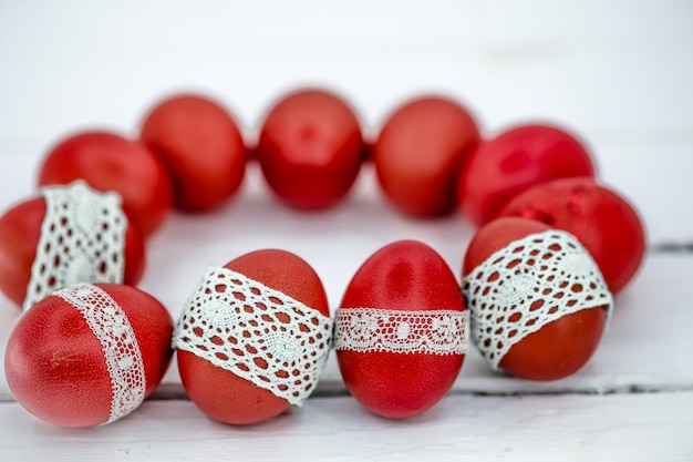 Uova di pasqua rosse su nastro di pizzo legato bianco, primo piano, sdraiato su un legno bianco