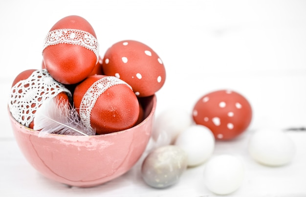 Red easter eggs on white tied lace tape, close-up