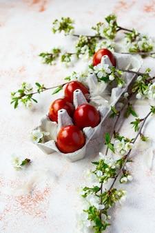 Красные пасхальные яйца с весенними цветочными бранчами на светло-бежевом фоне. вертикальный выстрел