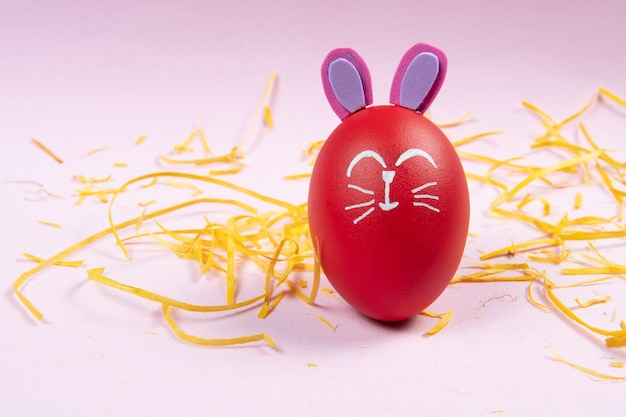 黄色いわらの削りくずに描かれたイースターウサギと赤い卵