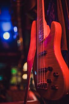 赤いエレクトリックギターと暗い背景にクラシックアンプ。