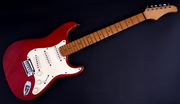 Red electric guitar with a black background.