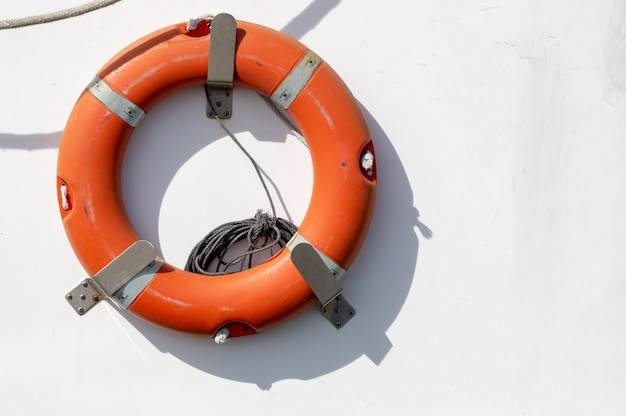Red emergency lifebuoy hanging on the side of a fishing boat.