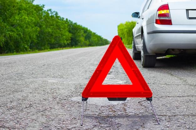 赤い緊急停止標識と道路上の壊れた銀車