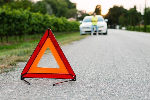 赤い緊急停止の標識と道路上の壊れた車で車の援助を待っている男