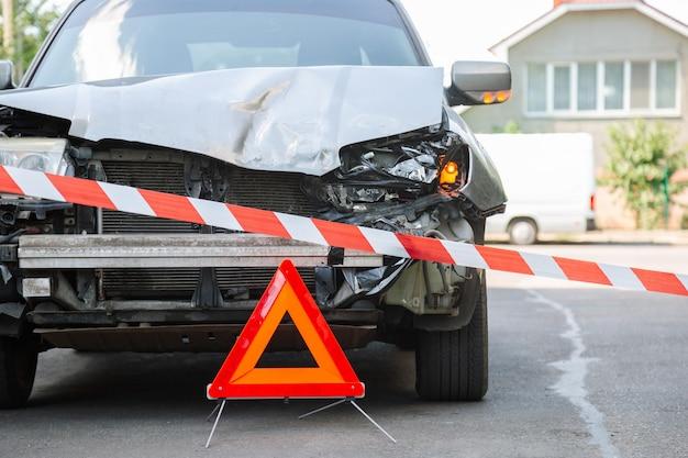 赤い緊急停止の三角形の標識と赤い警告警察テープが前にあります。都市道路での自動車事故で破壊された車。事故で壊れた車を壊した。壊れたヘッドライトを壊した。