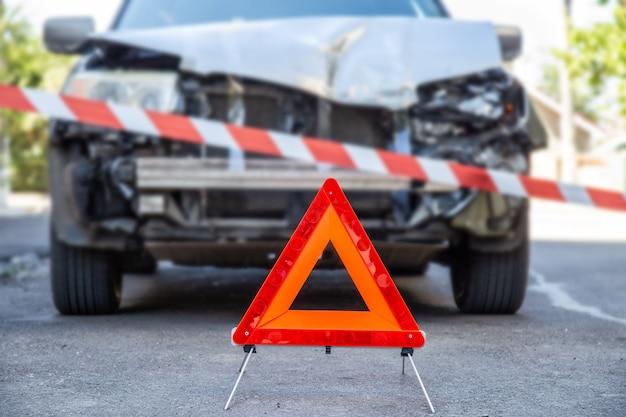 빨간색 비상 정지 삼각형 기호 및 빨간색 경고 경찰 테이프 전에 도시 도로에서 자동차 충돌 교통 사고에서 자동차를 파괴. 사고로 부서진 자동차.
